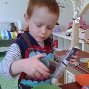 Mi hijo jugando a las cocinas en la ludoteca